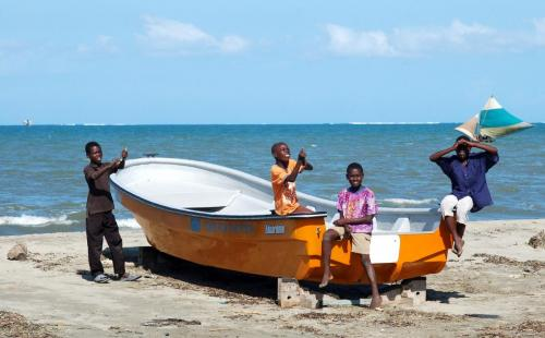 Haitian boys with kite on boat at beach