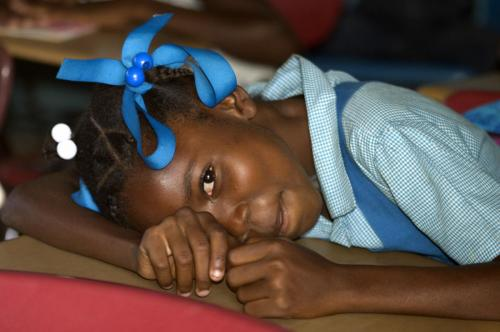 Haitian girl with head on desk