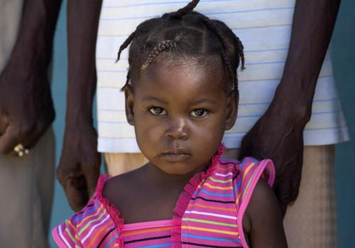 Little Haitian girl in pink dress with horizonal stripes